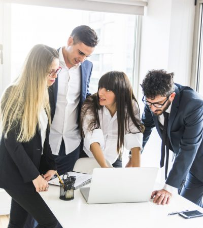group-businesspeople-standing-office-looking-laptop-office